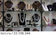 Купить «Colorful necklaces made from different precious stones for sale in jewelry store», видеоролик № 33198344, снято 31 октября 2019 г. (c) Яков Филимонов / Фотобанк Лори