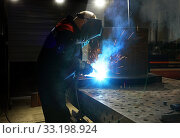 Купить «Metalworker in safety mask and gloves using welding torch to join sides of metal construction», фото № 33198924, снято 14 февраля 2020 г. (c) Алексей Кузнецов / Фотобанк Лори