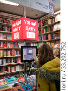 Moscow, Russia - Feb 21. 2020. Buyer in Biblio Globus - the largest and oldest book store in Russia. Редакционное фото, фотограф Володина Ольга / Фотобанк Лори