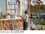 Купить «Рабочий устанавливает леса для ремонта облицовки деревянного дома в солнечный день», фото № 33203064, снято 19 сентября 2019 г. (c) Светлана Попова / Фотобанк Лори