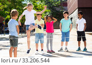 Купить «Happy smiling little friends playing with chinese jumping rope at playground», фото № 33206544, снято 8 апреля 2020 г. (c) Яков Филимонов / Фотобанк Лори