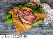 Купить «Piece of raw pork and vegetables on a wooden table», фото № 33207404, снято 21 февраля 2020 г. (c) Татьяна Ляпи / Фотобанк Лори