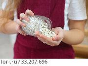 Купить «Children's hands hold a glass jar with white beans», фото № 33207696, снято 23 февраля 2020 г. (c) Марина Володько / Фотобанк Лори