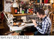 Купить «Professional man worker in leather workshop», фото № 33210232, снято 3 апреля 2020 г. (c) Яков Филимонов / Фотобанк Лори
