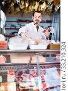Купить «Positive male butcher showing sorts of meat», фото № 33210324, снято 2 января 2017 г. (c) Яков Филимонов / Фотобанк Лори