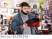 Satisfied man buys new pan in the hardware store. Стоковое фото, фотограф Яков Филимонов / Фотобанк Лори