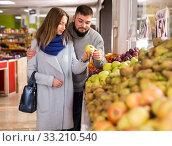 Купить «Friendly couple examining apples in grocery shop», фото № 33210540, снято 20 ноября 2019 г. (c) Яков Филимонов / Фотобанк Лори