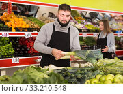 Купить «Male shop assistant lays fresh leek on counter in grocery shop», фото № 33210548, снято 20 ноября 2019 г. (c) Яков Филимонов / Фотобанк Лори