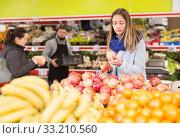 Купить «Portrait of positive woman buying ripe pomegranates in food store», фото № 33210560, снято 20 ноября 2019 г. (c) Яков Филимонов / Фотобанк Лори