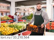Купить «Man seller moving box of oranges in grocery shop», фото № 33210564, снято 20 ноября 2019 г. (c) Яков Филимонов / Фотобанк Лори