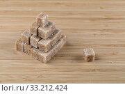 Кусочки тростникового сахара, выложенные в форме пирамидки на деревянной доске. Стоковое фото, фотограф Игорь Долгов / Фотобанк Лори
