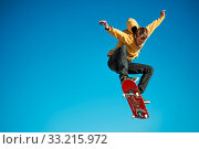Купить «A teenager skateboarder does an ollie trick in a skatepark on the outskirts of the city On a background of blue sky gradient», фото № 33215972, снято 25 февраля 2020 г. (c) easy Fotostock / Фотобанк Лори