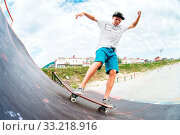 Купить «Young skater doing the trick over a ramp on a skateboard in a skate park. Wide angle», фото № 33218916, снято 7 июля 2020 г. (c) easy Fotostock / Фотобанк Лори