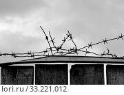 Купить «Barbed wire on dark fence. Monochrome silhouette photo», фото № 33221012, снято 1 апреля 2020 г. (c) easy Fotostock / Фотобанк Лори