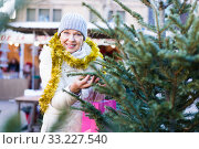 Купить «Woman is preparing for Christmas and choosing X-mas tree», фото № 33227540, снято 21 декабря 2017 г. (c) Яков Филимонов / Фотобанк Лори