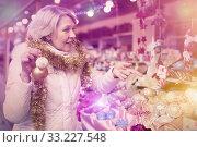 Купить «Smiling woman is buying toys for X-mas tree in the market», фото № 33227548, снято 21 декабря 2017 г. (c) Яков Филимонов / Фотобанк Лори