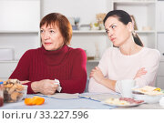 Unhappy adult female quarrel with daughter at table. Стоковое фото, фотограф Яков Филимонов / Фотобанк Лори