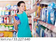 Woman choosing dishwashing liquid on supermarket shelf. Стоковое фото, фотограф Яков Филимонов / Фотобанк Лори