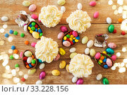 Купить «cupcakes with chocolate eggs and candies on table», фото № 33228156, снято 15 марта 2018 г. (c) Syda Productions / Фотобанк Лори