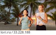 Купить «women or female friends with earphones running», фото № 33228188, снято 28 июля 2019 г. (c) Syda Productions / Фотобанк Лори