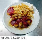 Купить «Berlin, Germany, curry sausage and French fries on one plate», фото № 33229104, снято 20 мая 2019 г. (c) Caro Photoagency / Фотобанк Лори