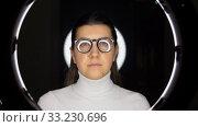 Купить «woman in glasses over white illumination on black», видеоролик № 33230696, снято 23 декабря 2019 г. (c) Syda Productions / Фотобанк Лори