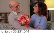 Купить «happy senior couple with bunch of flowers at home», видеоролик № 33231044, снято 4 января 2020 г. (c) Syda Productions / Фотобанк Лори
