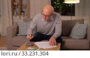 Купить «senior man counting money at home», видеоролик № 33231304, снято 4 января 2020 г. (c) Syda Productions / Фотобанк Лори