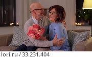 Купить «happy senior couple with bunch of flowers at home», видеоролик № 33231404, снято 4 января 2020 г. (c) Syda Productions / Фотобанк Лори