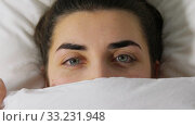 Купить «happy woman in bed peeking from under blanket», видеоролик № 33231948, снято 22 января 2020 г. (c) Syda Productions / Фотобанк Лори