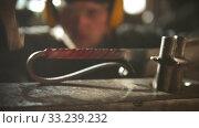 Купить «Blacksmith forging a metal handle for knife with unusual design», видеоролик № 33239232, снято 6 июня 2020 г. (c) Константин Шишкин / Фотобанк Лори