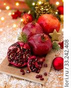 Купить «Fresh ripe pomegranates on wooden background and Christmas decoration.», фото № 33242408, снято 29 марта 2020 г. (c) PantherMedia / Фотобанк Лори