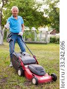 Купить «Positive elderly man with lawnmower when mowing the lawn», фото № 33242696, снято 30 мая 2020 г. (c) Яков Филимонов / Фотобанк Лори