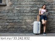 Traveling happy girl standing on wall background. Стоковое фото, фотограф Яков Филимонов / Фотобанк Лори