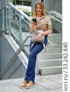 Купить «Young positive smiling woman reading from mobile phone screen in metro», фото № 33242840, снято 31 марта 2019 г. (c) Яков Филимонов / Фотобанк Лори