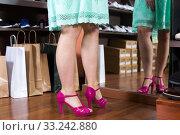 Купить «Customer is trying on pink heeled sandals near mirror», фото № 33242880, снято 10 мая 2017 г. (c) Яков Филимонов / Фотобанк Лори