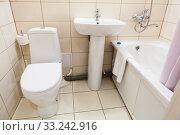 Simple half bathroom with toilet, sink and bath with shower, white sanitary ware. Стоковое фото, фотограф Кекяляйнен Андрей / Фотобанк Лори