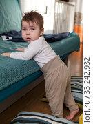 Купить «Toddler child starts to stand on his legs, holding sofa, soft pillows are around for safety falling», фото № 33242932, снято 7 февраля 2020 г. (c) Кекяляйнен Андрей / Фотобанк Лори