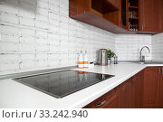 Interior of domestic kitchen with cooktop electric touch stove and long white tabletop with sink. Стоковое фото, фотограф Кекяляйнен Андрей / Фотобанк Лори