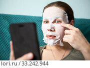 Купить «Young Caucasian woman applying face rejuvenating mask using smartphone as mirror», фото № 33242944, снято 15 февраля 2020 г. (c) Кекяляйнен Андрей / Фотобанк Лори