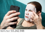 Rejuvenating mask applying with the help of camera of smartphone, woman looking at phone screen during skin care procedure. Стоковое фото, фотограф Кекяляйнен Андрей / Фотобанк Лори