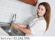Купить «Housewife washing an apple in kitchen sink, long hair woman in white blouse», фото № 33242956, снято 27 июля 2015 г. (c) Кекяляйнен Андрей / Фотобанк Лори