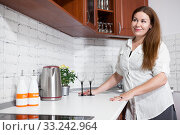 Satisfied woman standing next to tabletop in kitchen with two wineglasses, preparing in expectation of meeting. Стоковое фото, фотограф Кекяляйнен Андрей / Фотобанк Лори
