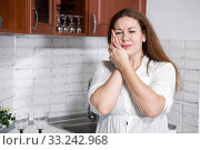 Young woman with toothache standing in kitchen, holding her cheek with hands. Стоковое фото, фотограф Кекяляйнен Андрей / Фотобанк Лори