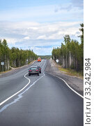 Купить «Highway stretches away to mountains on horizon. Passenger cars driving on the Kola asphalt road. It is way to the Murmansk city on north of Russia», фото № 33242984, снято 16 июля 2015 г. (c) Кекяляйнен Андрей / Фотобанк Лори