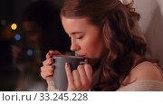 Купить «young woman drinking coffee or tea at window», видеоролик № 33245228, снято 21 января 2020 г. (c) Syda Productions / Фотобанк Лори