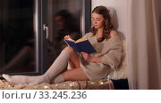 Купить «woman reading book sitting on windowsill at home», видеоролик № 33245236, снято 21 января 2020 г. (c) Syda Productions / Фотобанк Лори