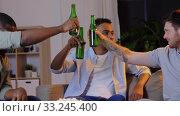 Купить «male friends drinking beer and watching tv at home», видеоролик № 33245400, снято 12 января 2020 г. (c) Syda Productions / Фотобанк Лори