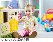 Купить «Cute toddler baby playing with busy board in daycare. Children's educational toys.», фото № 33259448, снято 27 мая 2020 г. (c) Оксана Кузьмина / Фотобанк Лори
