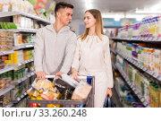 Купить «Smiling man and woman with shopping cart», фото № 33260248, снято 7 ноября 2019 г. (c) Яков Филимонов / Фотобанк Лори